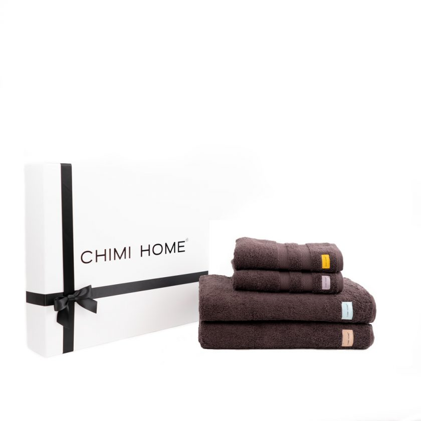 Four brown nicely folded terry towels from Chimi Home which lie in front of a black and white gift box