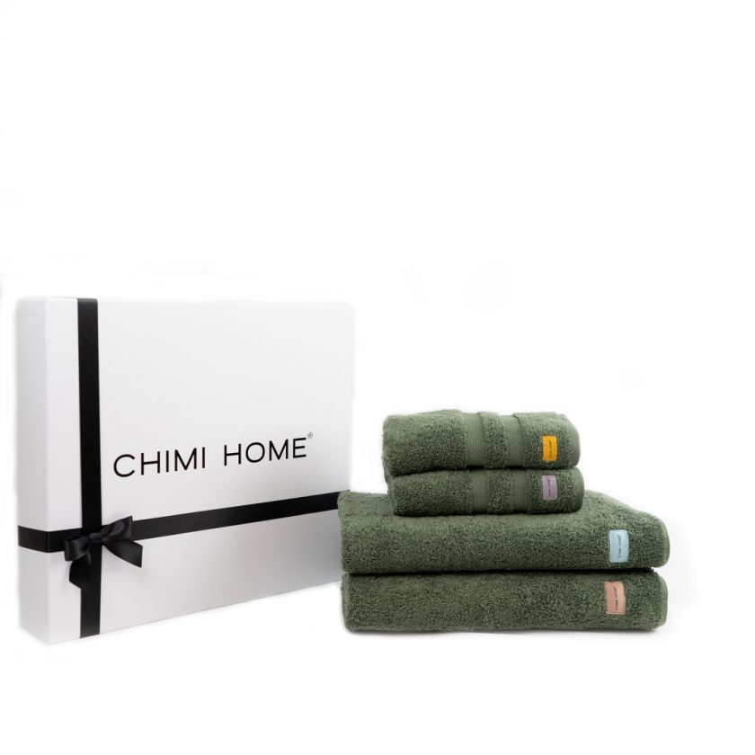 Four green nicely folded terry towels from Chimi Home lying in front of a black and white gift box