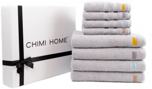 Eight gray towels laid on top of each other and a chemistry home box to show what is included in our gift boxes