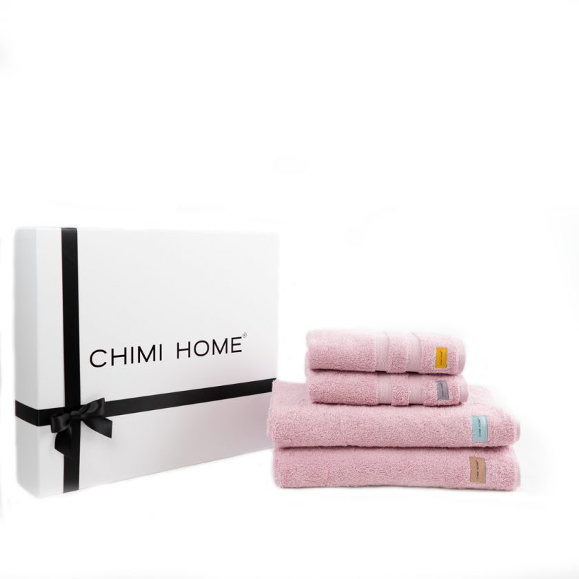 Four pink nicely folded towels in terry from Chimi Home which lies in front of a black and white gift box